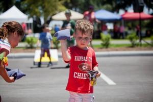 little boy wearing Kansas City Chiefs shirt playing bean bag toss